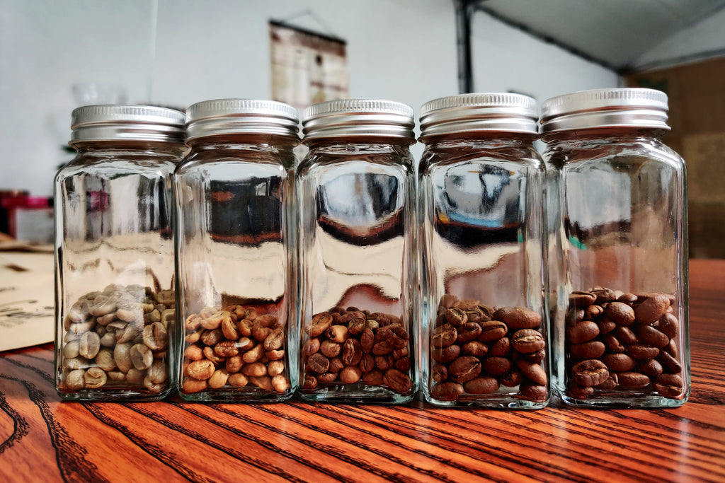 glass jars each containing a variety of coffee beans