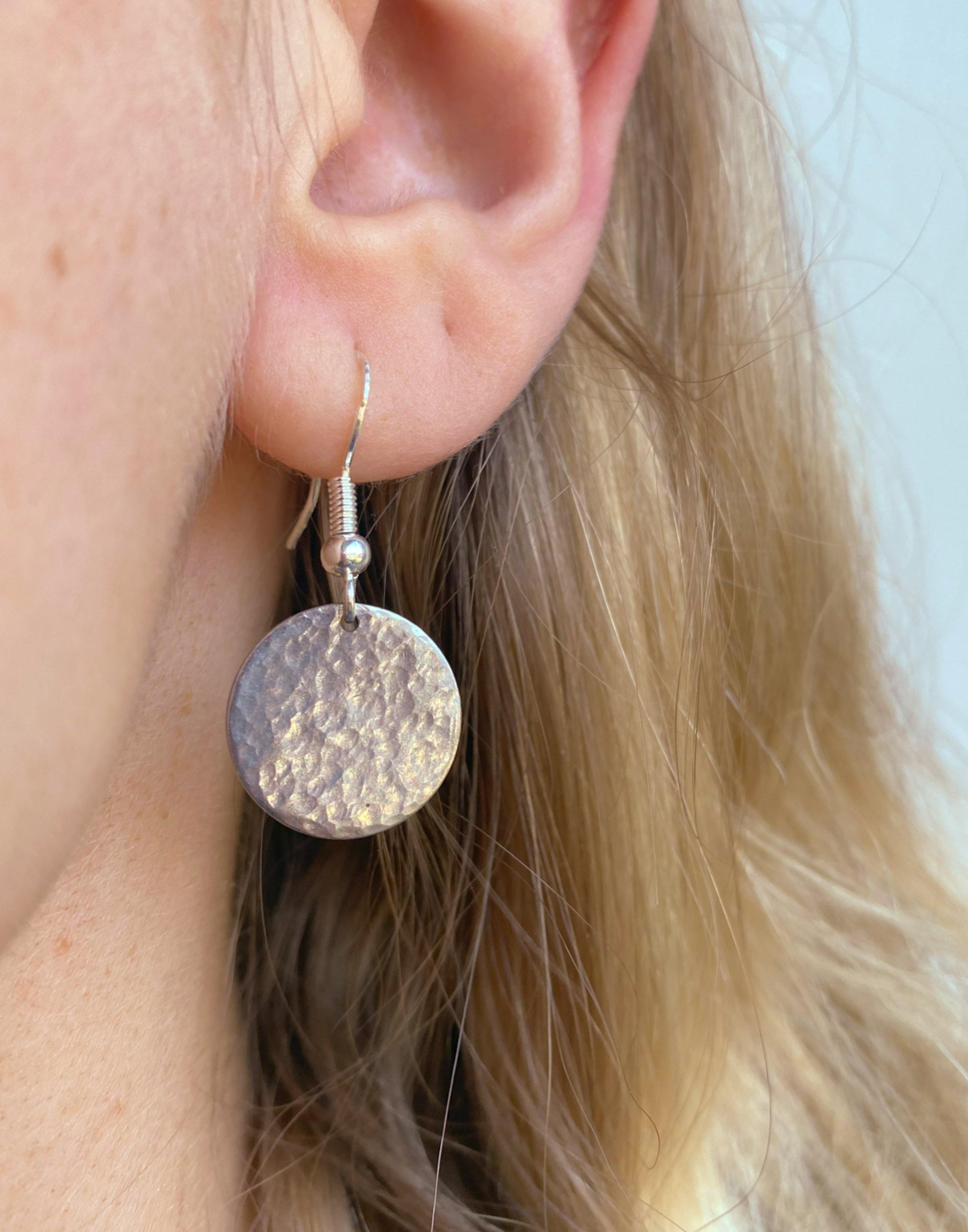 Close up of Silver Dangle Earrings in a womans ear