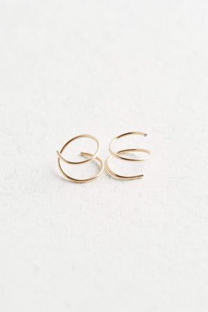 Gold hoop earrings on a white surface