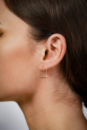Close up of woman wearing gold square hoop earrings
