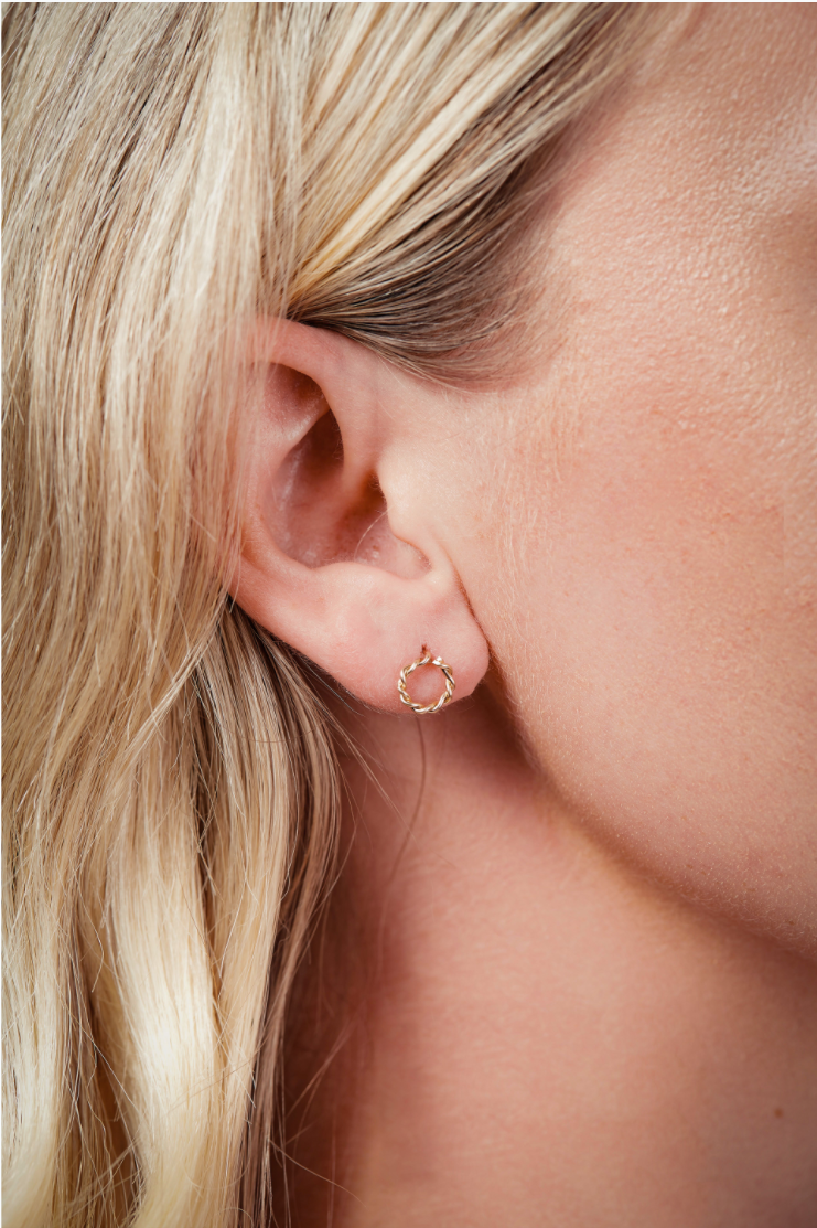 Close up of gold stud earrings in a womans ear