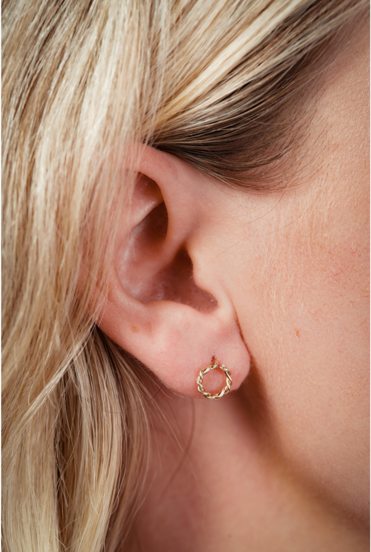 Close up of 14k Gold Twisted Stud Earrings in a womans ear