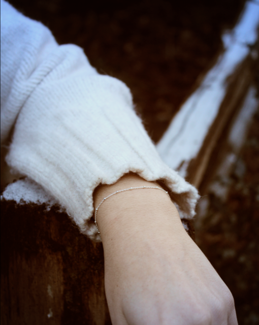 Woman wearing a silver chain bracelet and resting arm on a fence