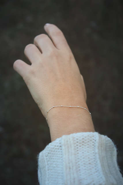 Woman wearing silver satellite chain bracelet with arm in the air