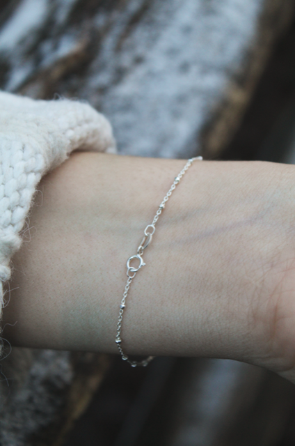 Close up of silver chain bracelet on womans wrist