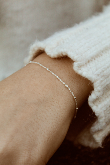 Close up of woman wearing silver chain bracelet