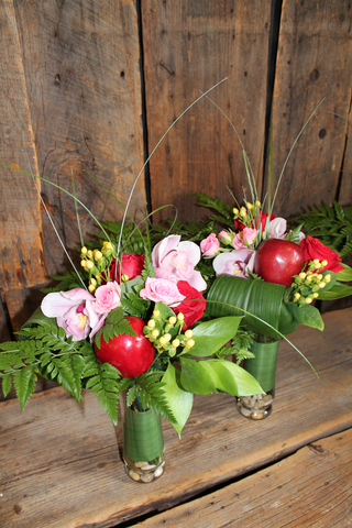 These slender vases carry a delightful arrangement of apples, roses and orchids