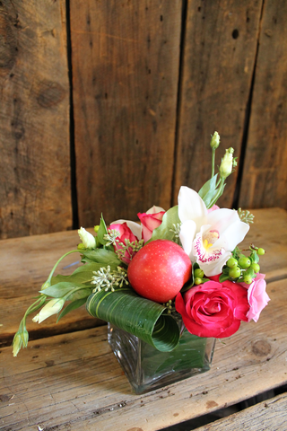Small modern arrangement in a square vase using Isareli lisianthus, perfect for the holidays