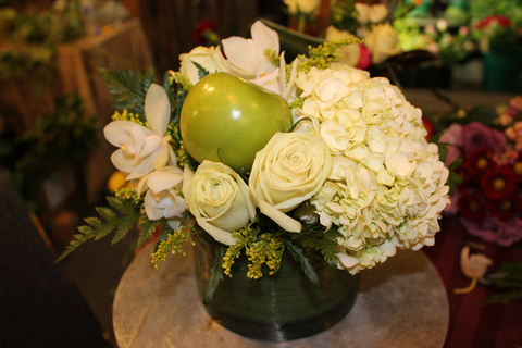 A fresh white and green round arrangement with apples and hydrangea
