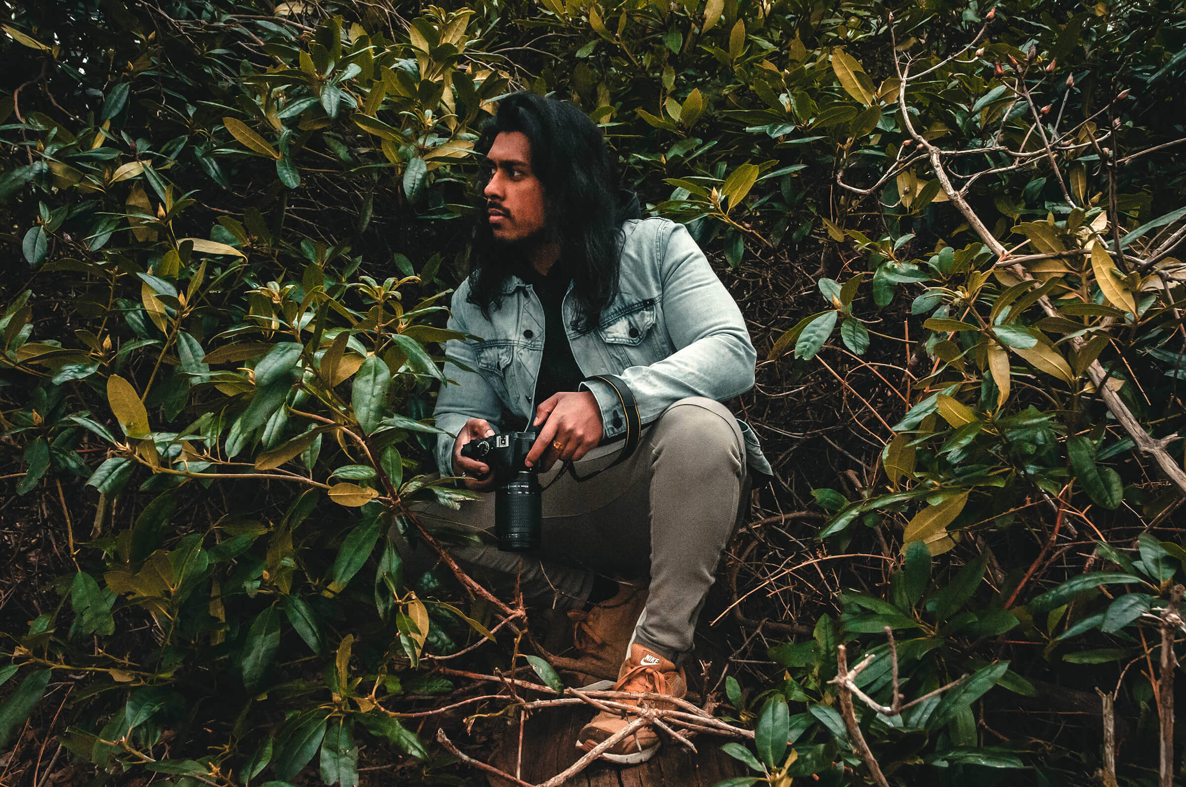 Photographer Crouching In The Woods