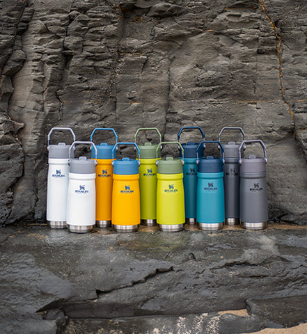 Stanley IceFlow™ Flip Straw Water Bottles in Polar, Saffron, Aloe, Lagoon, and Charcoal on the beach.