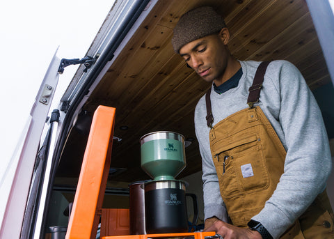 Elijah making pour over coffee in his Dodge RAM ProMaster 2500