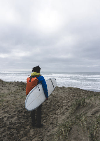 Adam looks out over the ocean holding a surfboard in Newport, Oregon.