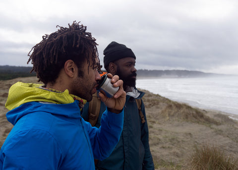 Adam and Kenny looking out at the break at South Jetty, Newport Oregon. Adam drinks out of the cup lid of a Stanley vacuum bottle.