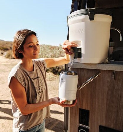 Woman camping with her family, filling Stanley's IceFlow™ Flip Straw Jug from The Fast Flow Water Jug.