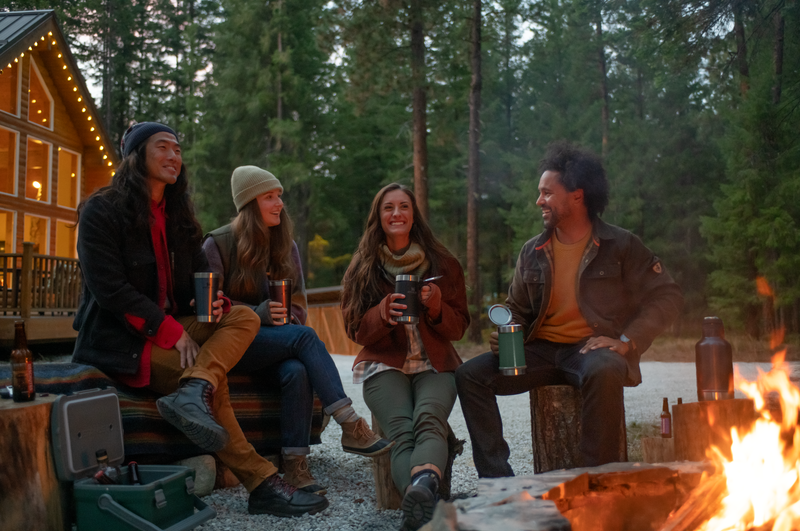 A group of adults sitting around a campfire, smiling.