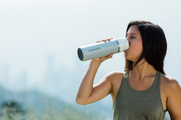A person in a grey tank top drinking from a Stanley water bottle.