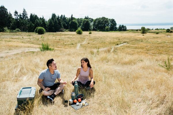 Two campers sitting around a picnic in a field.