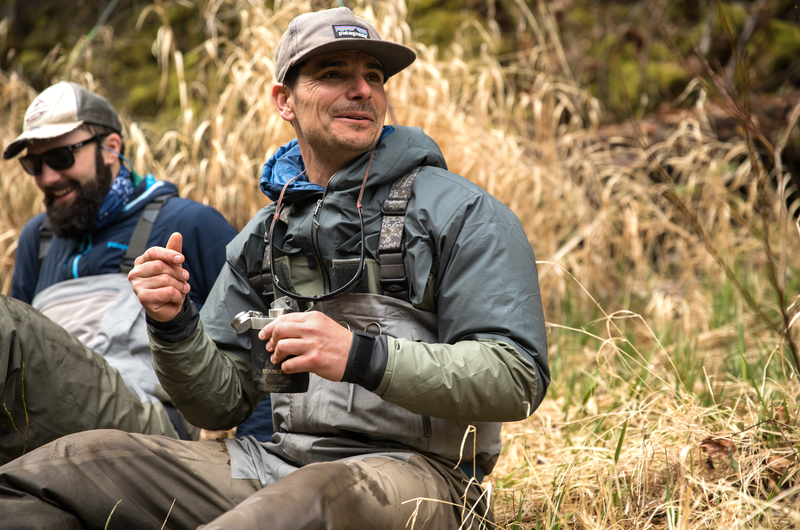 Two veterans dressed in adventure gear sit outside in the wilderness.