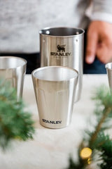 Stanley cocktail shaker with two stainless-steel shot glasses on a table.