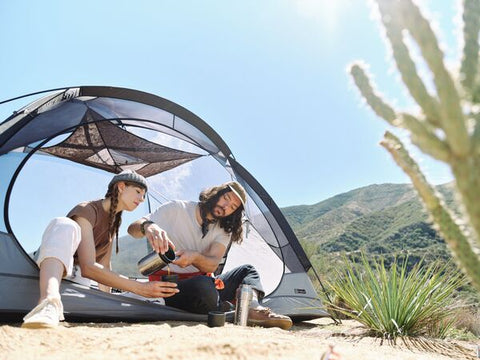 Couple camping in the desert using Stanley's Bowl+Spork Compact Cook Set.
