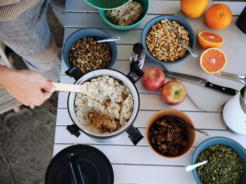 Camping table set for breakfast with oatmeal served from the Stanley Adventure Stay-Hot Camp Crock.