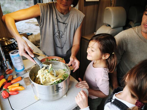 Mother with family in RV making pasta with Stanley's stainless-steel, Even-Heat Camp Pro Cook Set.