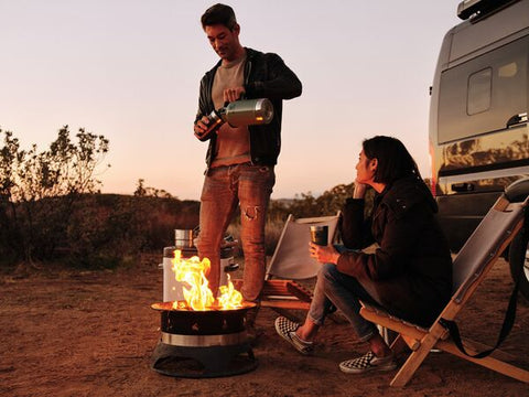 Man standing next to campfire, serving beer from Stanley's insulated Easy-Pour Growler in Hammertone Green.