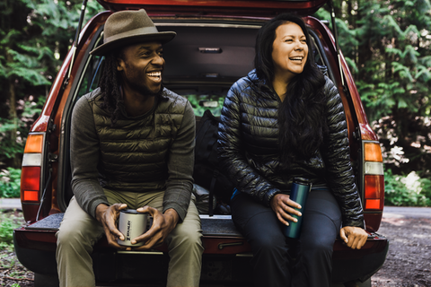 Man and woman sitting on the tailgate of a station wagon, each holding a Stanley titanium mug.