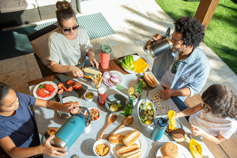 Mother with family enjoying a backyard picnic with colorful drinkware from Stanley's IceFlow™ Flip Straw Collection.