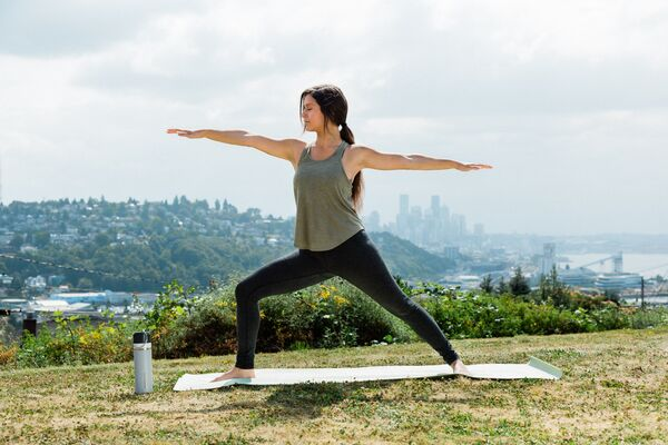 A person stands in a yoga warrior 2 pose in a natural environment with an urban landscape in the background.