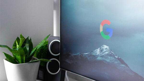 Google Smart Home: Google Logo On A Computer Screen With Speaker and Plant In Background