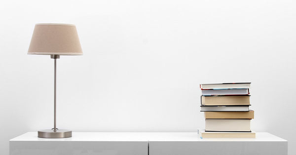 Why You Should Have A Smart Light Switch In Your Home: Lamp Next To A Stack of Books