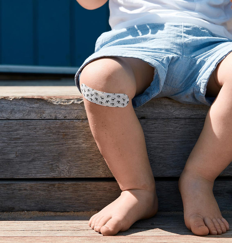 Toddler sitting on step in the sun with coconut oil Patch strip on his knee