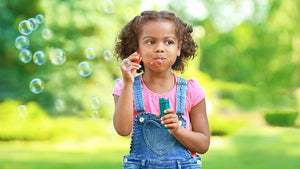 Young girl wearing denim overalls blowing bubbles outside.