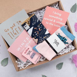 Gift box showing products inside the box. Including positive affirmation, socks, milk chocolate, planner, you are enough pin