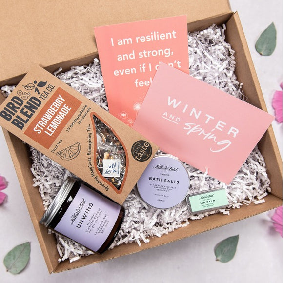 gift box with images inside the gift box. including positive affirmations, tea, candle, bath salts and lip balm