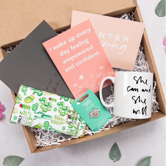 Image of products inside the gift box. Including positive affirmation, planner, milk chocolate, Strong AF pin and mug