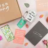Gift box with products including mug, planner, strong AF pin, chocolate and positive affirmation arranged outside of the box