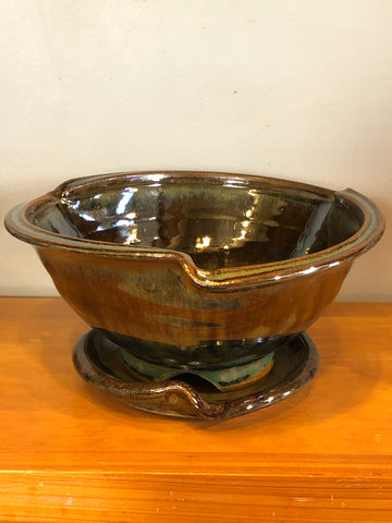 Strainer-style bowl with decorative rim treatment, and sitting on a tray with a similar decorative rim treatment.