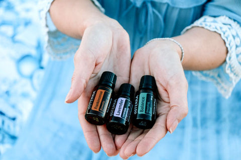 Woman holding three essential oils after purchase