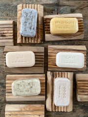 Rectangular french soaps on top of rectangular olive wood, ridged soap holders.