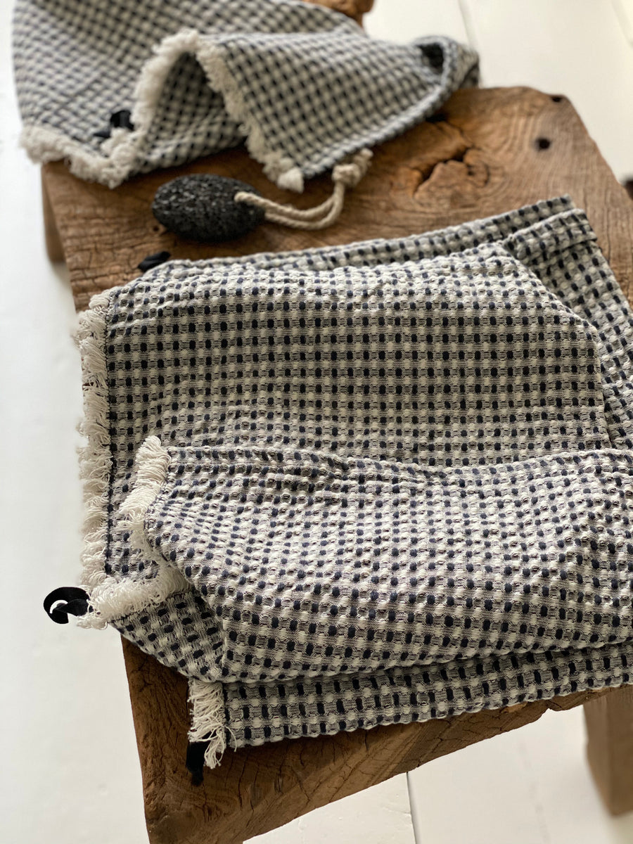 Waffle textured towels with a mottled black and white pattern. White frayed fringe and a black hanging loop.