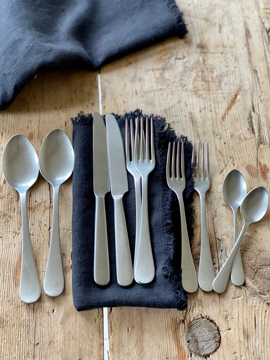Brushed stainless steel cutlery displayed on an antique dining table with dark, frayed edge, linen napkins.