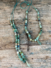 blue and green sea glass bead necklace with a small glass pendant hanging in the middle. twisted yarn fastening. long length.