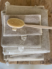 A stack of linen towels in natural colour. Each towel has a hanging loop in matching natural colour. Displayed with a beech back brush, hand loop on the back and long handle.