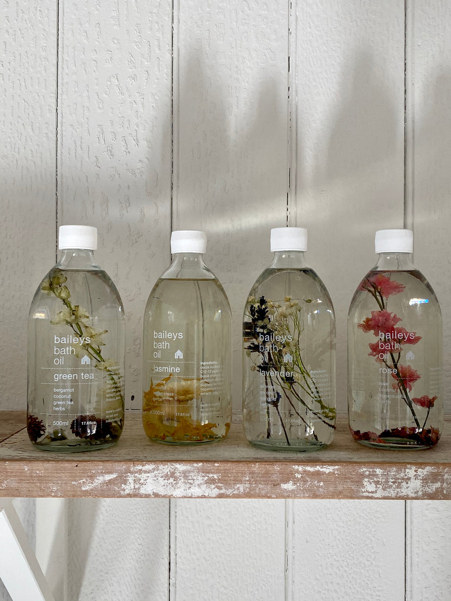 green tea, jasmine, lavender and rose bath oils in a clear glass bottle, white lid. Dried flowers to match each fragrance are suspended in the transparent oil.