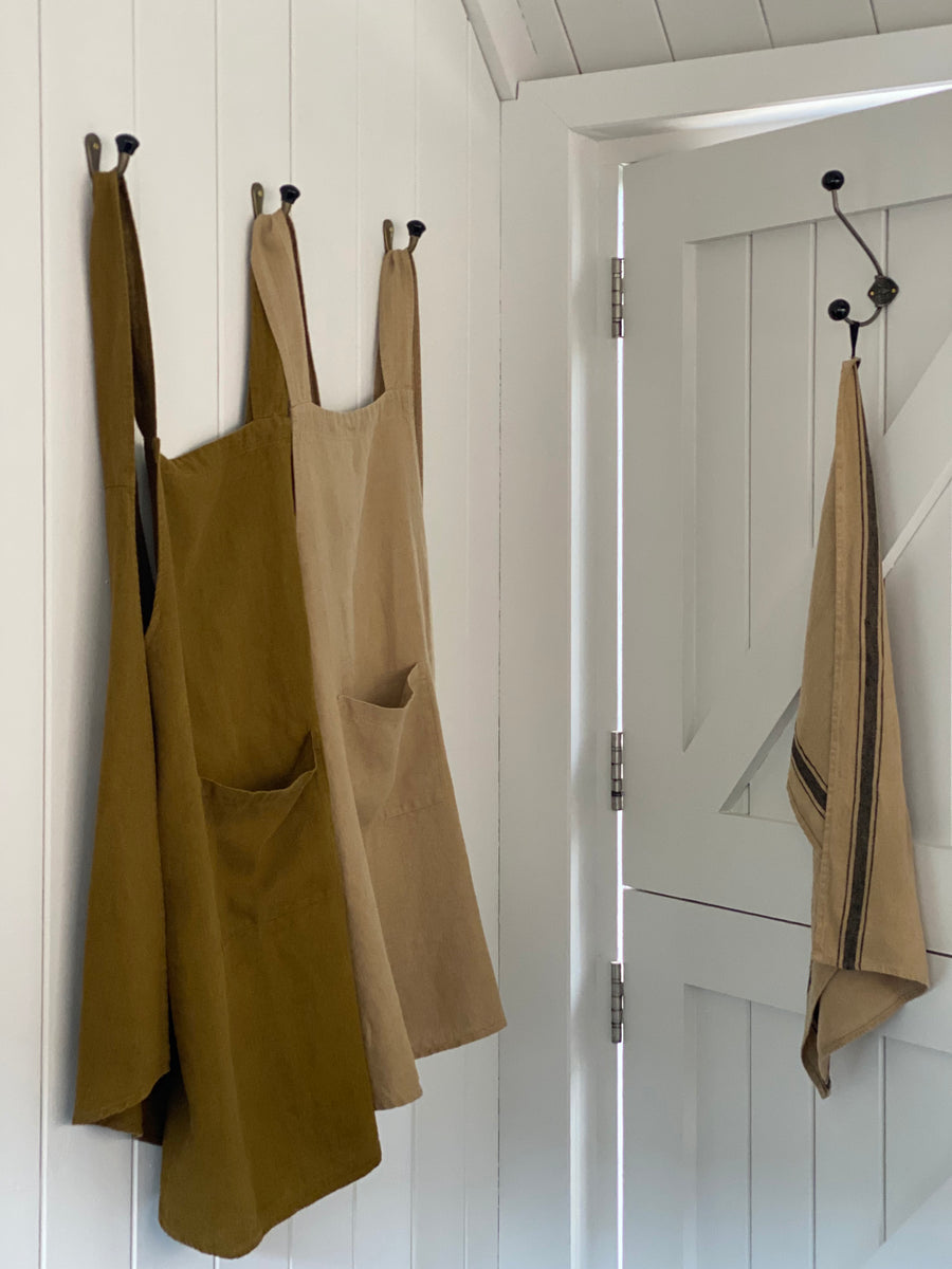 Ochre and sand coloured, cross-over linen aprons with pockets, displayed on wall hooks. Sand linen tea towel displayed on coat hook.