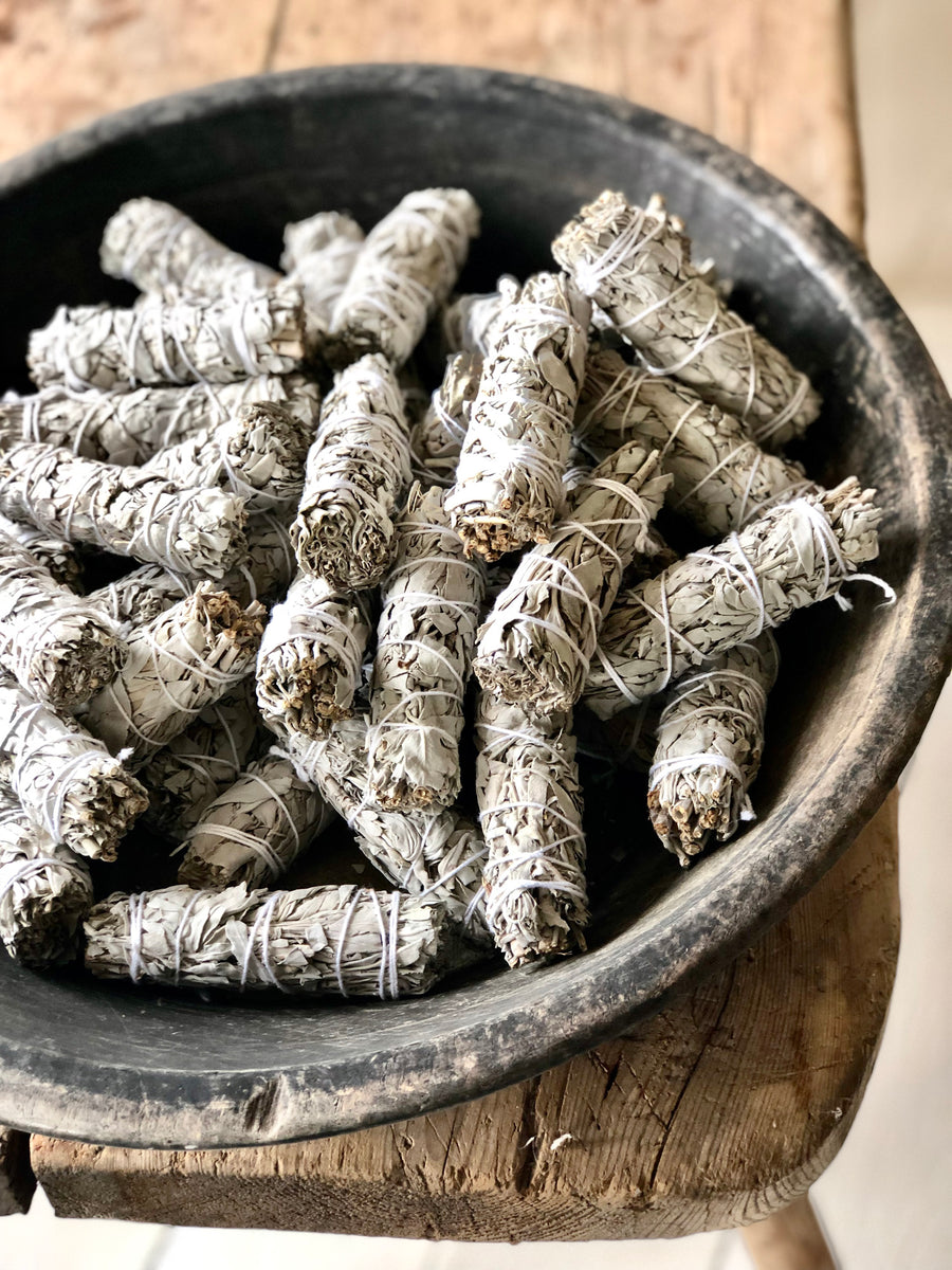 Bundles of dried white sage tied with string. Displayed in a bowl.