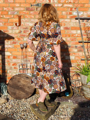 Jen, a white woman wearing a multicoloured midi dress, standing in front of a red brick wall with her back to the camera